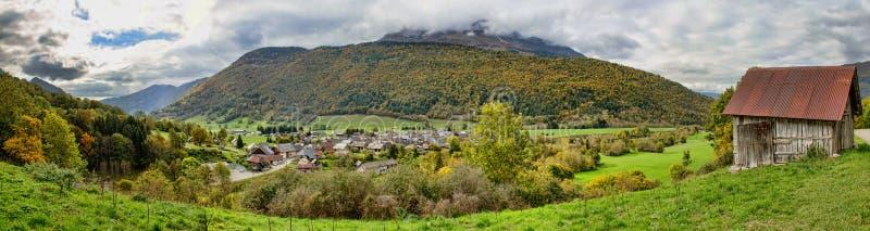Montaña hermosa del otoño y pequeño pueblo encendido fotografía de archivo