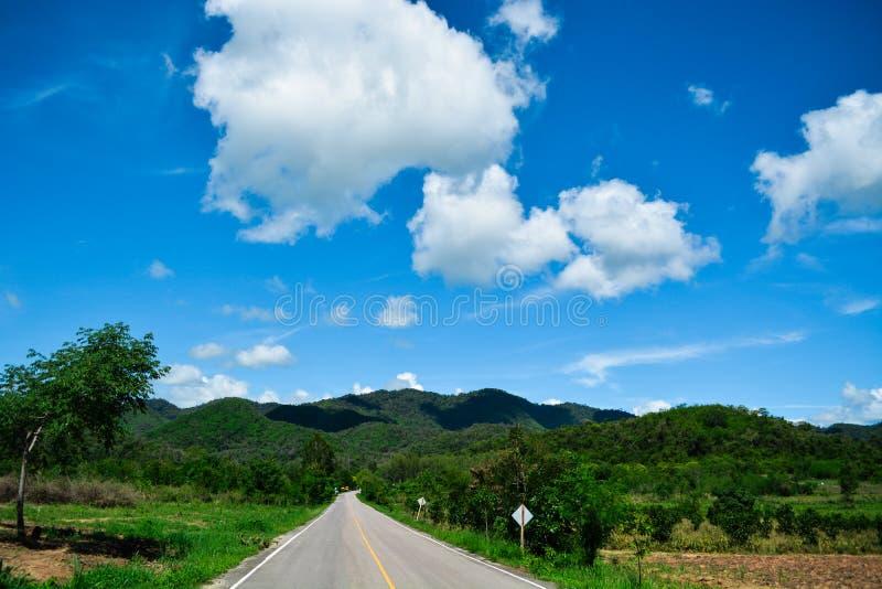montaña, las nubes del cielo y el camino imagen de archivo
