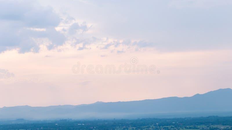 Montañas azules con niebla y edificios en la ciudad con el bosque, o fotos de archivo