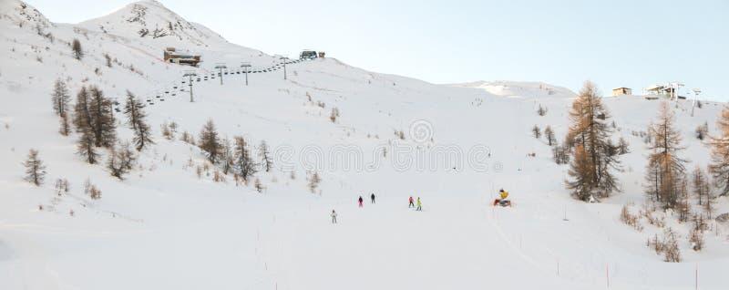 Montañas con nieve y esquiadores en invierno en Sauze D 'Oulx Piamonte imagenes de archivo
