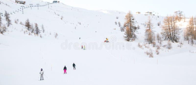Montañas con nieve y esquiadores en invierno en Sauze D 'Oulx Piamonte imagen de archivo