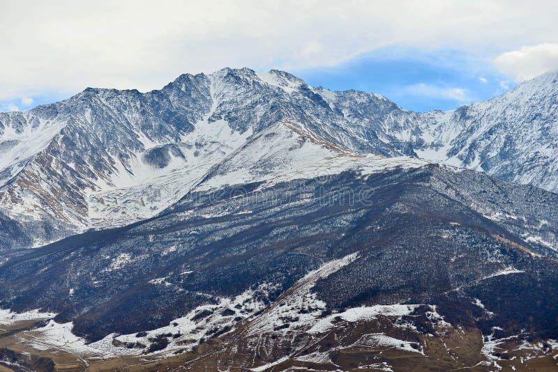 Montañas coronadas de nieve rocosas sobre el pueblo de Fiagdon foto de archivo