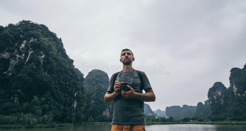 Montañas de desatención de la piedra caliza del hombre caucásico en la provincia de Ninh Binh, Vietnam d?a nublado imagenes de archivo
