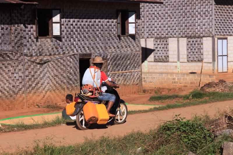 Montañas de Kalaw, Myanmar - 18 de noviembre de 2019: Aldeanos locales que conducen en la moto a través de un pueblo en las monta fotografía de archivo