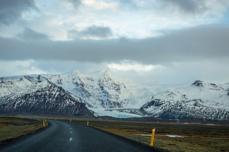 Montañas de la nieve y carreteras islandesas imágenes de archivo libres de regalías