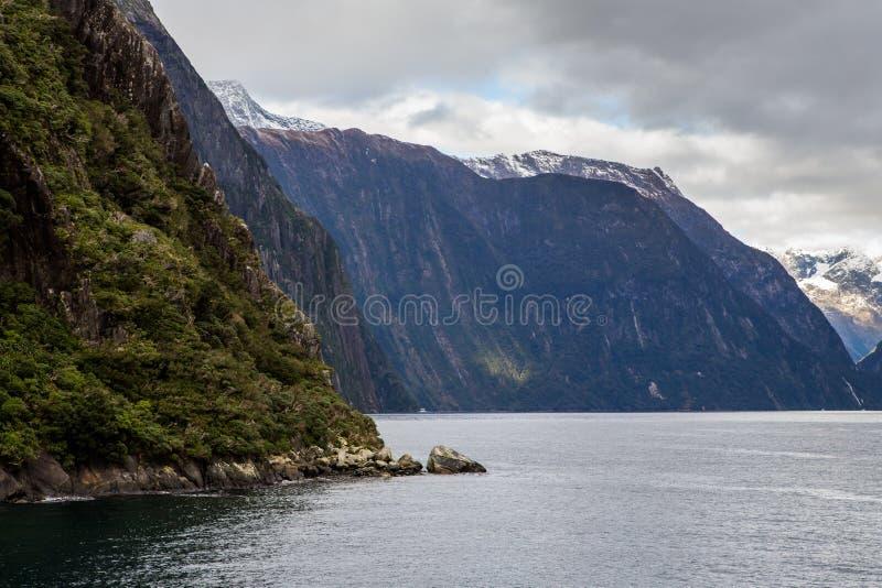 Montañas de Milford Sound en agua imagen de archivo