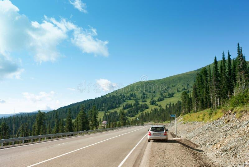 Montañas de Sayany La pista Día asoleado del verano El coche parado en el borde de la carretera foto de archivo libre de regalías