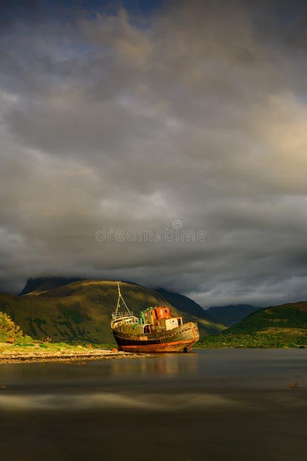 Montañas del paisaje de Escocia, del barco abandonado del pescador y de Ben Nevis en la puesta del sol imagen de archivo libre de regalías
