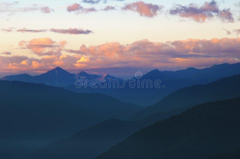 Montañas después de la puesta del sol con el cielo y las nubes hermosos foto de archivo