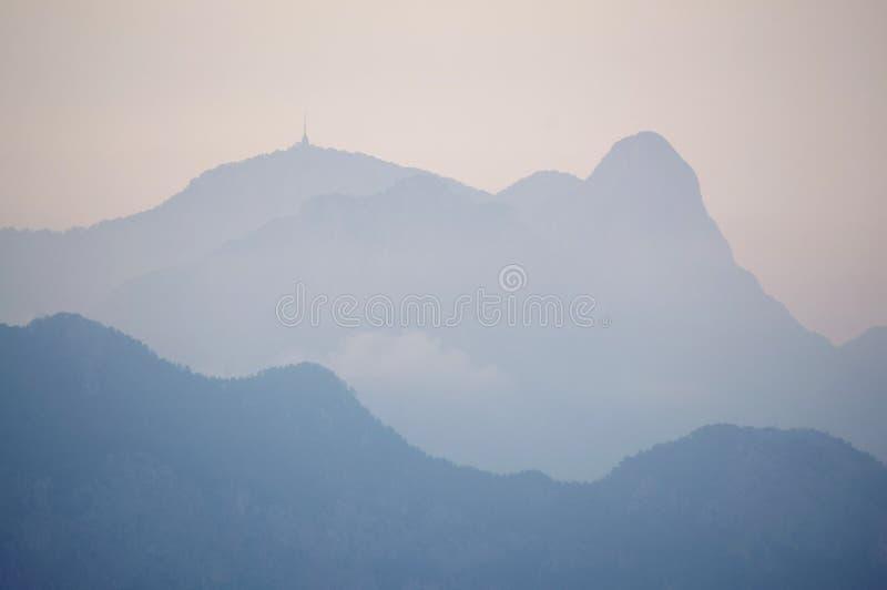 Montañas distantes borrosas de niebla en la oscuridad de la tarde imágenes de archivo libres de regalías