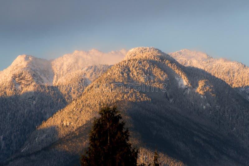 Montañas en nieve con la luz anaranjada de la salida del sol o del susnet foto de archivo libre de regalías