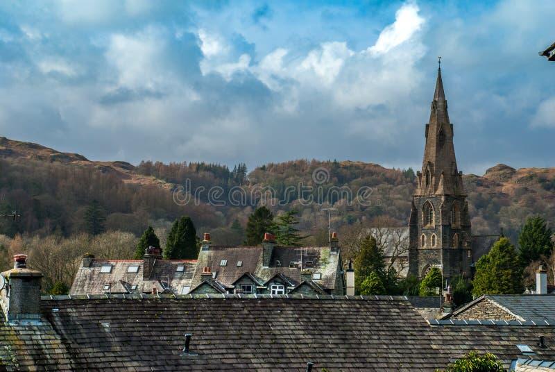 Montañas hermosas que miran a través del tejado de la casa y del top de la iglesia en el distrito del lago foto de archivo