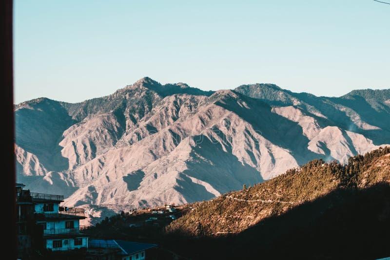 Montañas hermosas y una colina con las pequeñas casas imágenes de archivo libres de regalías