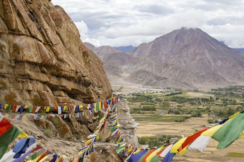 Montañas Himalayan y banderas budistas coloridas del rezo en el stupa cerca del monasterio budista en Ladakh, la India foto de archivo