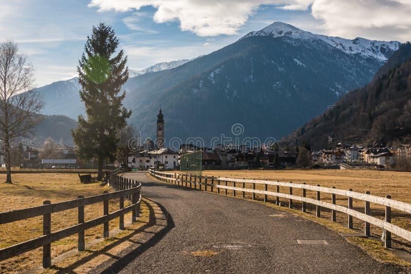 Montañas italianas, carretera de asfalto cercada con una cerca de madera que lleva al pueblo alpino fotos de archivo