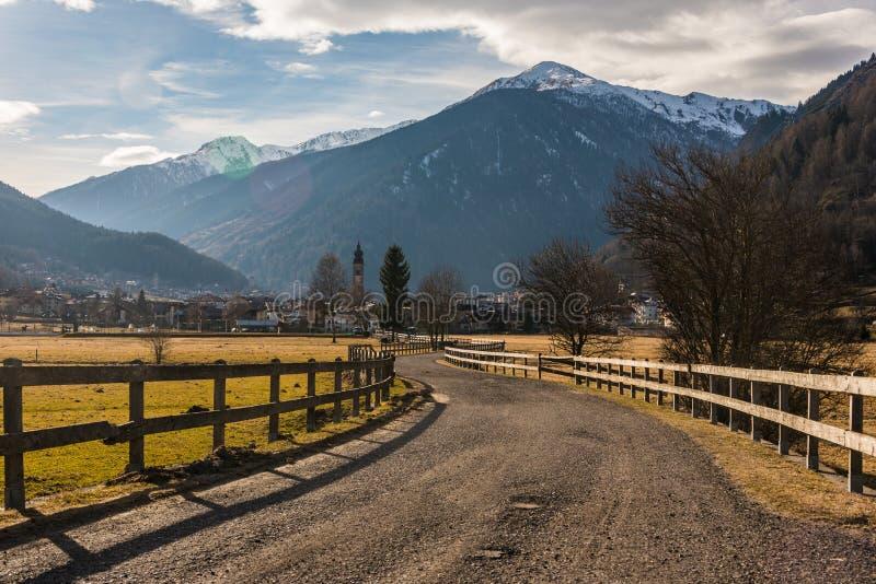 Montañas italianas, carretera de asfalto cercada con una cerca de madera que lleva al pueblo alpino fotografía de archivo libre de regalías