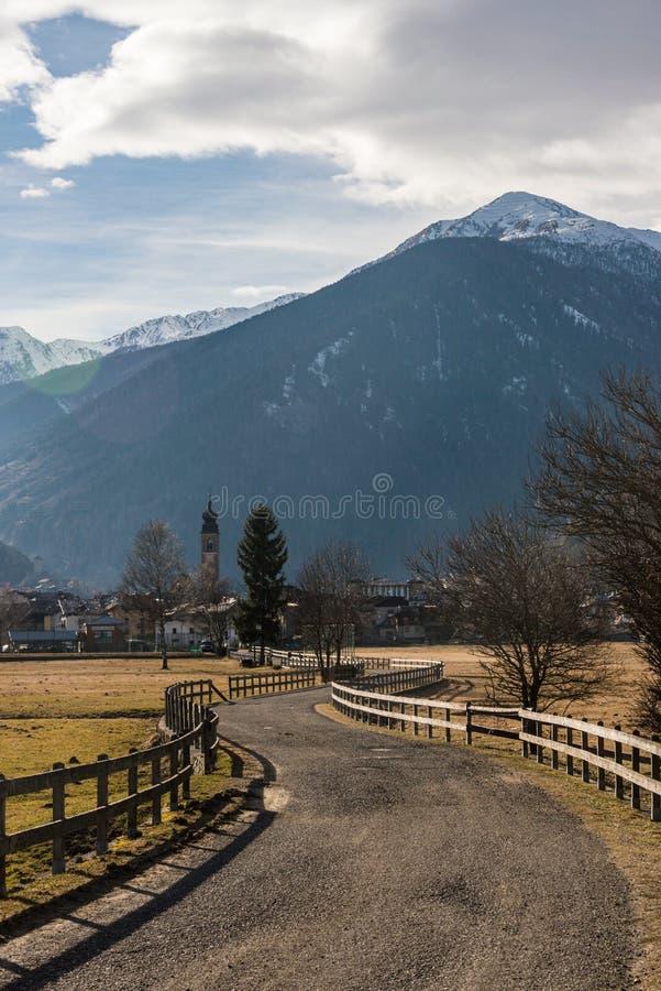 Montañas italianas, carretera de asfalto cercada con una cerca de madera que lleva al pueblo alpino imagenes de archivo