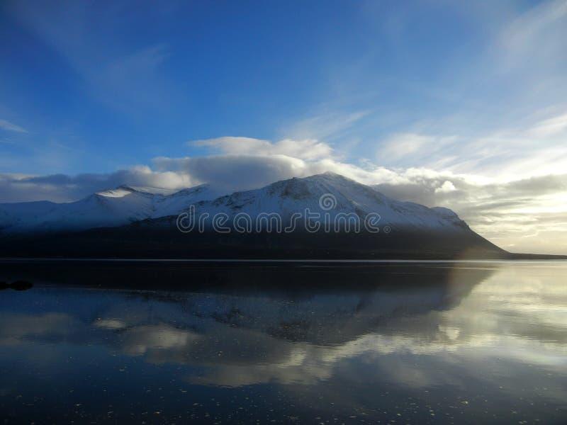 Montañas Nevado duplicadas en un fiordo fotos de archivo