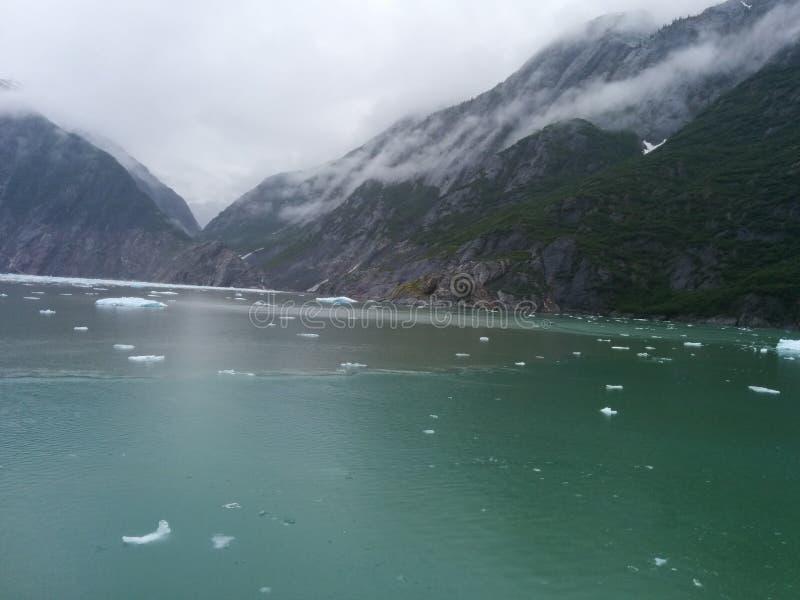 Montañas, océano y pequeño iceberg fotos de archivo