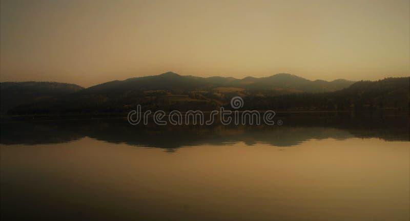 Montañas reflectoras del café de Montana de la salida del sol caliente calmante de la mañana imagenes de archivo