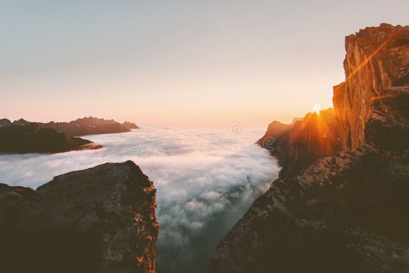 Montañas rocosas del paisaje de la puesta del sol sobre las nubes imagenes de archivo