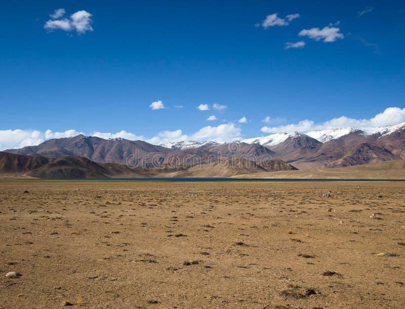 Montañas rocosas y valle chamuscado en un fondo del cielo azul fotografía de archivo