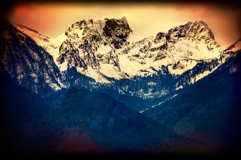 Montañas Suiza del invierno en sol Foto vieja en el papel amarillo fotografía de archivo