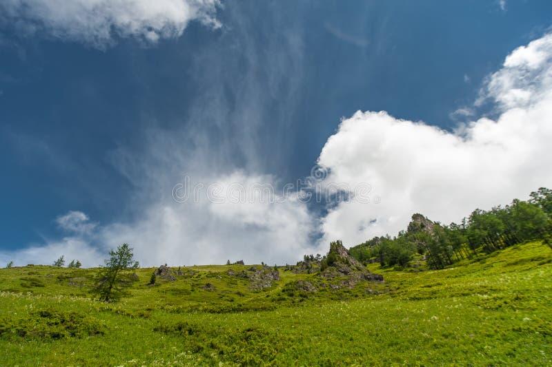 Montañas verdes con las nubes coloridas y el cielo azul imágenes de archivo libres de regalías