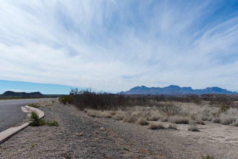 Montañas y árbol en el desierto cerca de un camino imagen de archivo