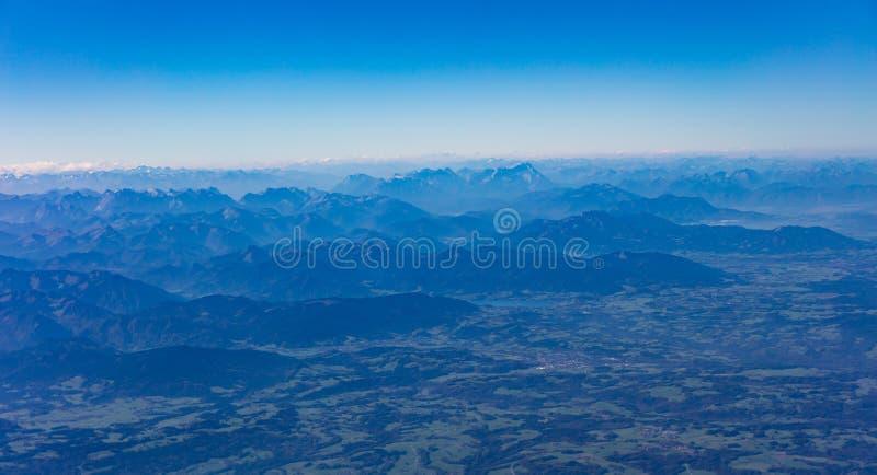Montañas y cielo azul desde arriba Visión fuera de una ventana del aeroplano fotografía de archivo