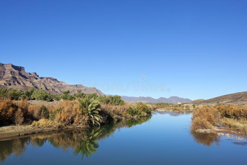 Montañas y río contra el cielo azul claro. fotografía de archivo