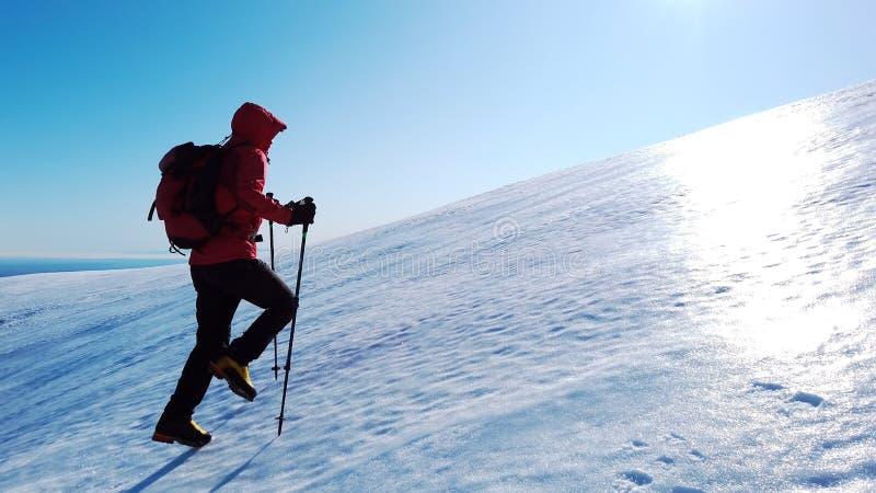Montañero sube una montaña nevada sobre un cielo azul claro Invierno foto de archivo libre de regalías