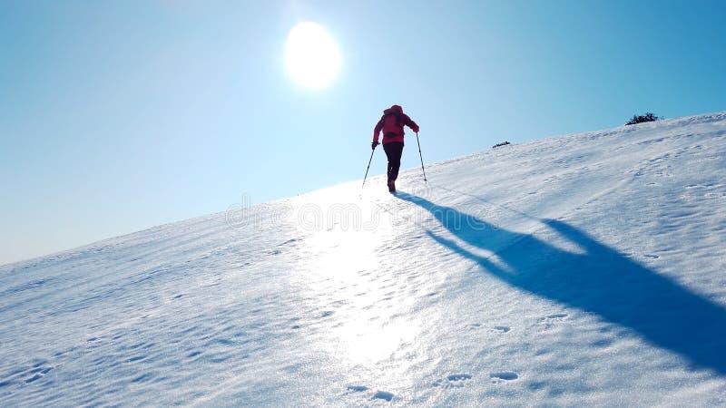 Montañero sube una montaña nevada sobre un cielo azul claro Invierno fotografía de archivo