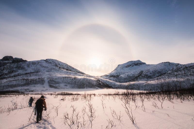 Montañeses que emigran en el valle de la nieve con halo del sol en invierno imagen de archivo libre de regalías