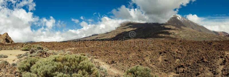 Monta?a Teide con los puntos blancos de la nieve, cubiertos en parte por las nubes Cielo azul brillante Parque nacional de Teide, foto de archivo