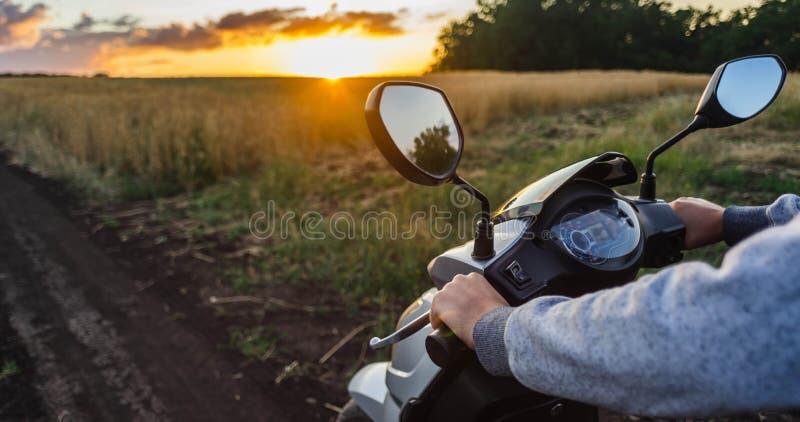 Montada ao longo de uma estrada vazia na floresta contra o céu do por do sol Volante do 'trotinette' e close up do velocímetro O  imagens de stock