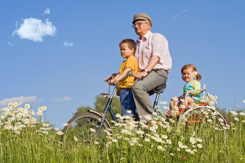 Montada com grandpa em uma bicicleta imagem de stock