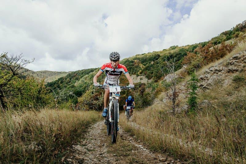 Montada de dois ciclistas dos cavaleiros subida em um fundo das montanhas e das nuvens imagem de stock royalty free