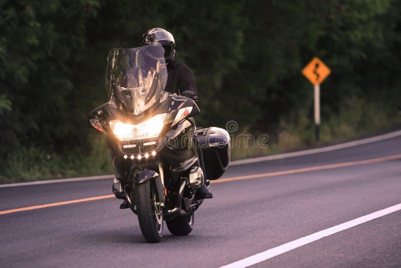 Montada do homem novo grande motorcycly no uso da estrada asfaltada fotos de stock royalty free