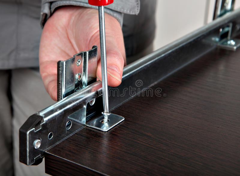 A montagem da mobília, instala as corrediças da gaveta, parafusando o parafuso foto de stock