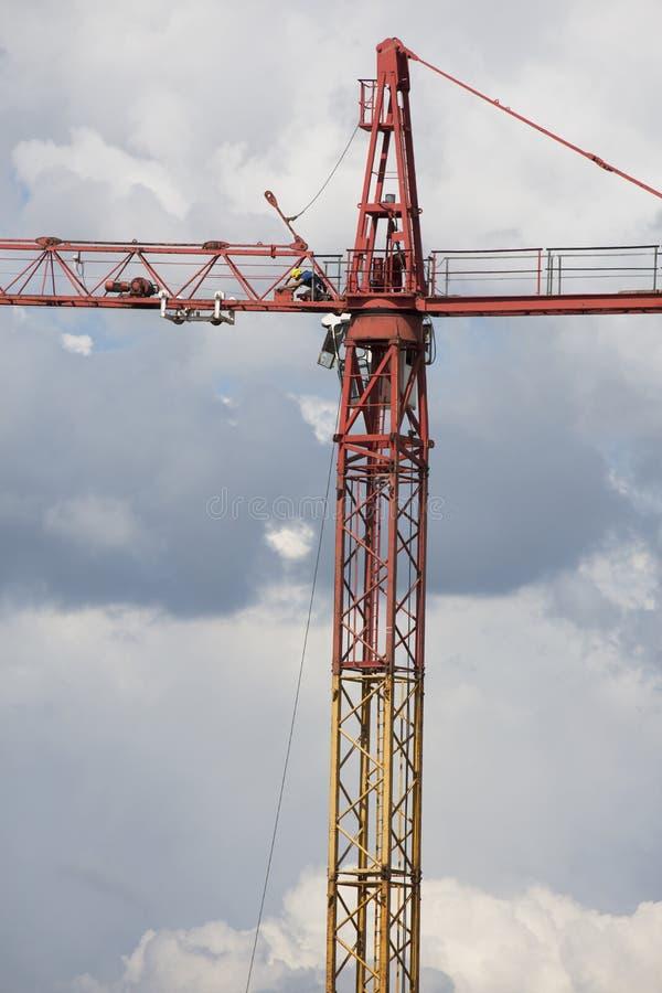 Montaggio della gru su fondo nuvoloso drammatico Situazione pericolosa di altezza immagini stock
