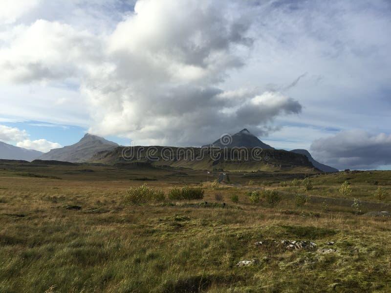 Montagna, campo di erba con il cielo nuvoloso, Islanda fotografia stock