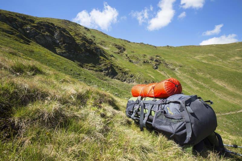 Montagna che fa un'escursione l'attrezzatura dello zaino sull'erba con la La della montagna fotografia stock libera da diritti