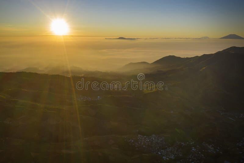 Montagna con il villaggio ad alba sul plateau di Dieng immagini stock libere da diritti