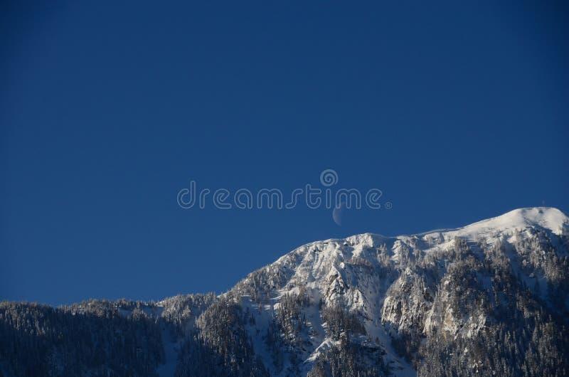 Montagna con neve e luna sul cielo fotografie stock