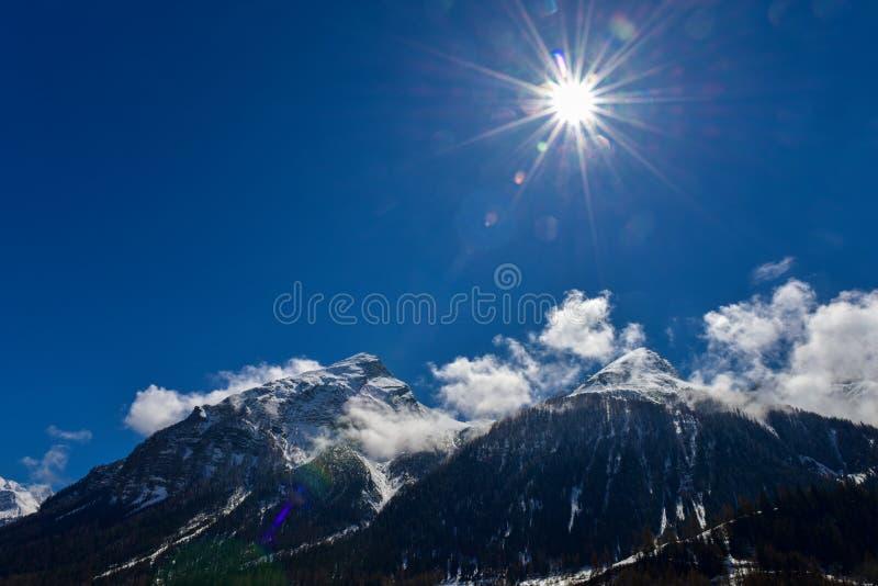 Montagna con neve sulla cima fra cielo blu e parasole immagine stock libera da diritti