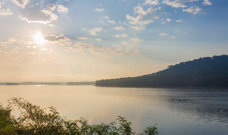 Montagna del paesaggio con la nebbia di acqua della nuvola del sole del cielo blu ed il fondo dell'albero fotografia stock libera da diritti