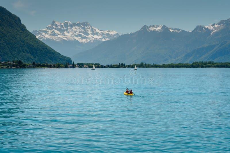 Montagna delle alpi e paesaggio svizzeri del lago Lemano con la rematura turistica sul lago in un kajak giallo immagine stock libera da diritti