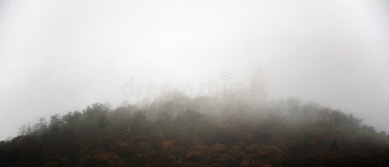 Montagna di Hnevin con il castello sotto nebbioso vicino alla maggior parte della città in repubblica Ceca autunnale il 4 novembr fotografie stock