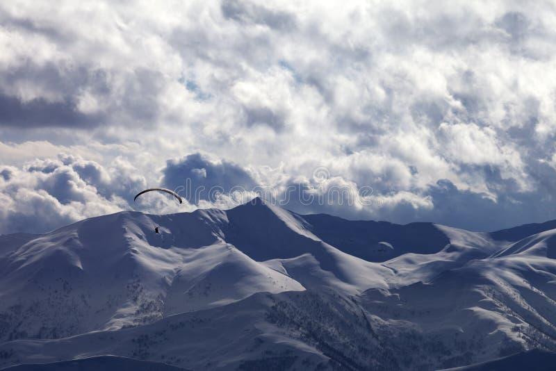 Montagna di luce solare di sera con le nuvole e la siluetta di paraglid fotografia stock